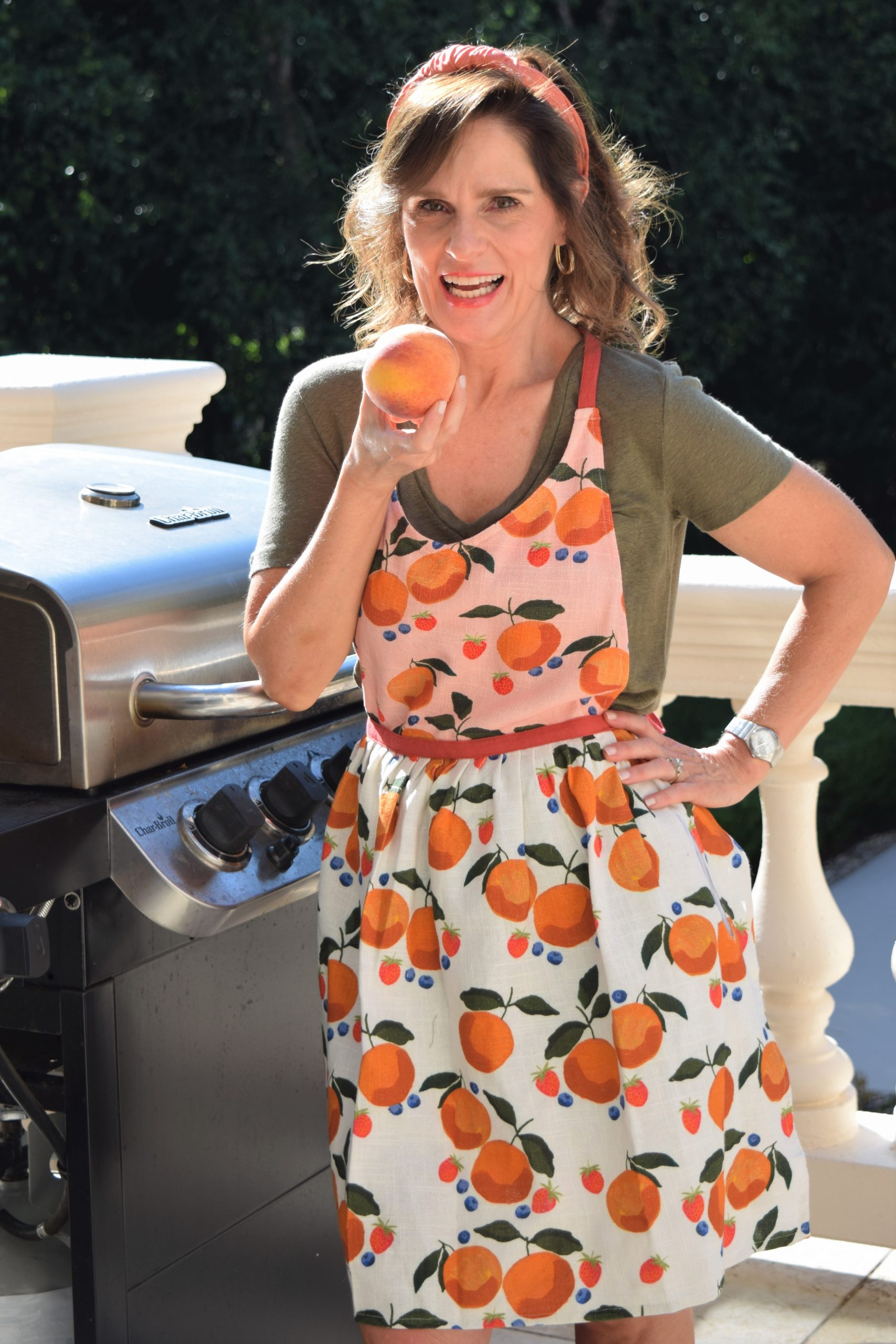 brunette woman over 50 standing in front of a grill wearing a retro style apron with peaches on it and holding a peach up to her mouth