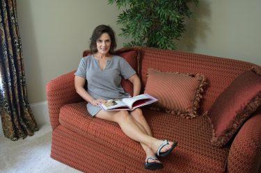 woman sitting on sofa reading wearing a t-shirt dress