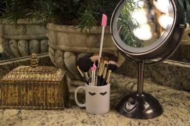 coffee mug with eyelashes painted on it sitting on a bathroom countertop filled with makeup brushes and pink Spatties