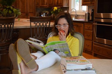 woman over 50 wearing a yellow shirt eating an apple and reading a cookbook