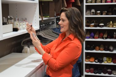 woman over 50 wearing an orange button down shirt standing in a closet smelling a perfume bottle