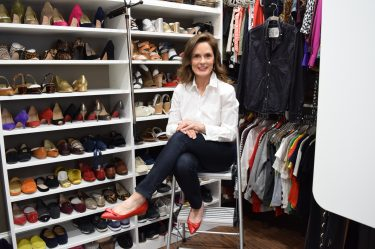 woman over 50 sitting on a step ladder in a closet with a wall of shoes behind her