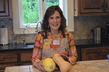 woman over 50 standing at a kitchen countertop wearing a pink and orange plaid top and a fall floral themed apron with a butternut squash, a spaghetti squash and an acorn squash in front of her