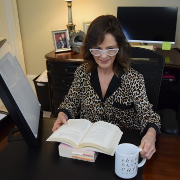 woman over 50 wearing leopard print pajamas sitting at a desk reading a book for morning me time a lightbox is next to her and she is holding a coffee cup