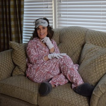 woman over 50 reclining on a beige small sofa wearing red paisley pajamas grey slippers a grey sleep mask and white cotton gloves for sleeping