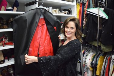 brunette woman over 50 wearing a black sweater showing a red leather jacket that is inside a breathable garment storage bag
