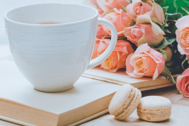 white coffee mug sitting on top of a book and next to pink roses macaroons are next to the book