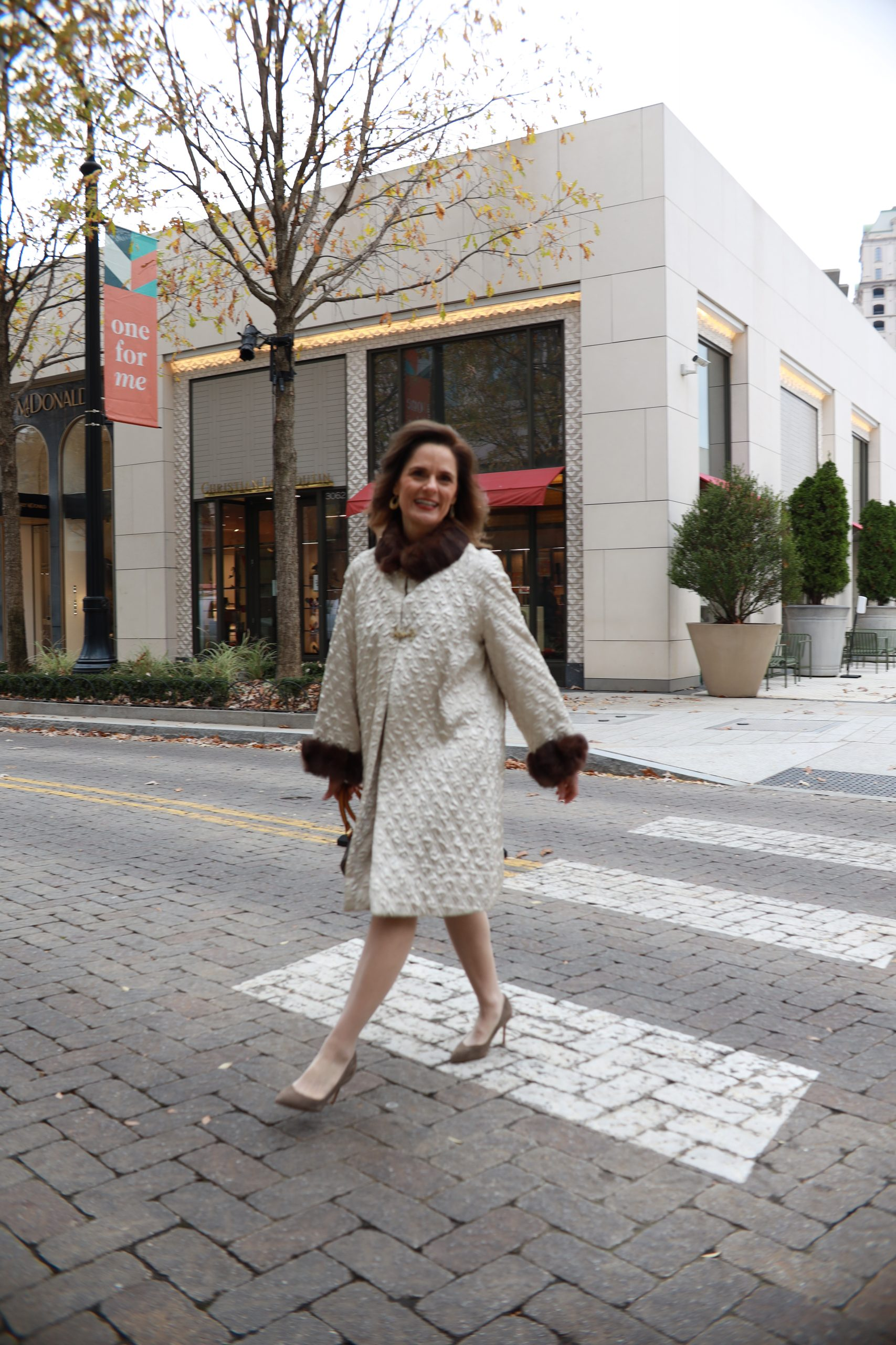 woman over 50 wearing a cream vintage fur trimmed coat walking across a street in a crosswalk in a shopping district