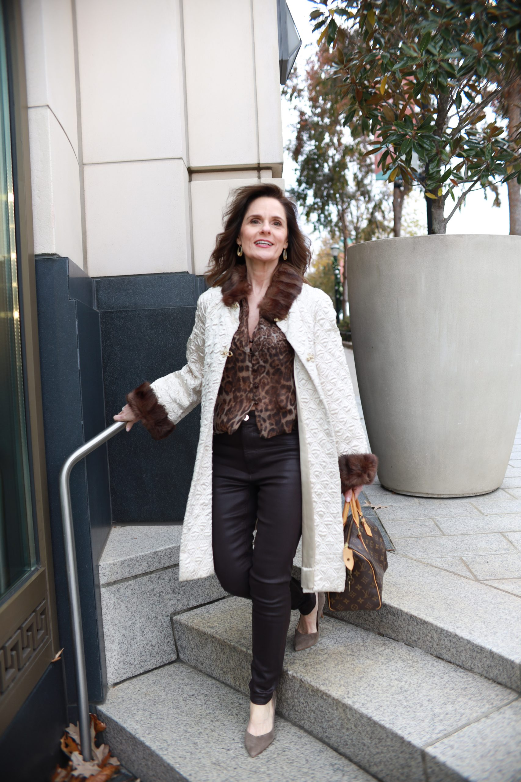 brunette over 50 woman wearing a vintage coat trimmed in fur a leopard print blouse and brown pants walking down an outdoor stairway