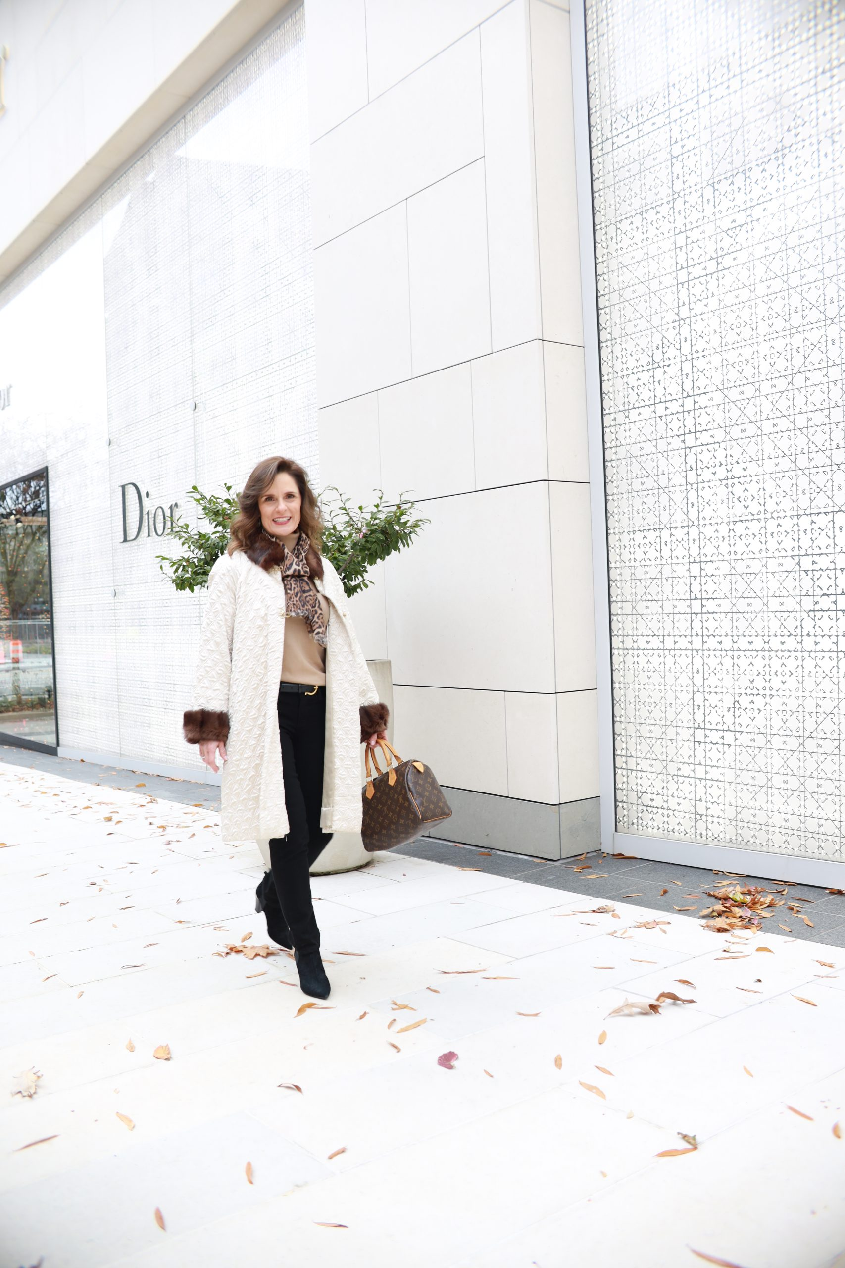 brunette over 50 woman wearing a cream vintage coat trimmed in fur with black pants a camel sweater and a leopard scarf in front of a white Dior store