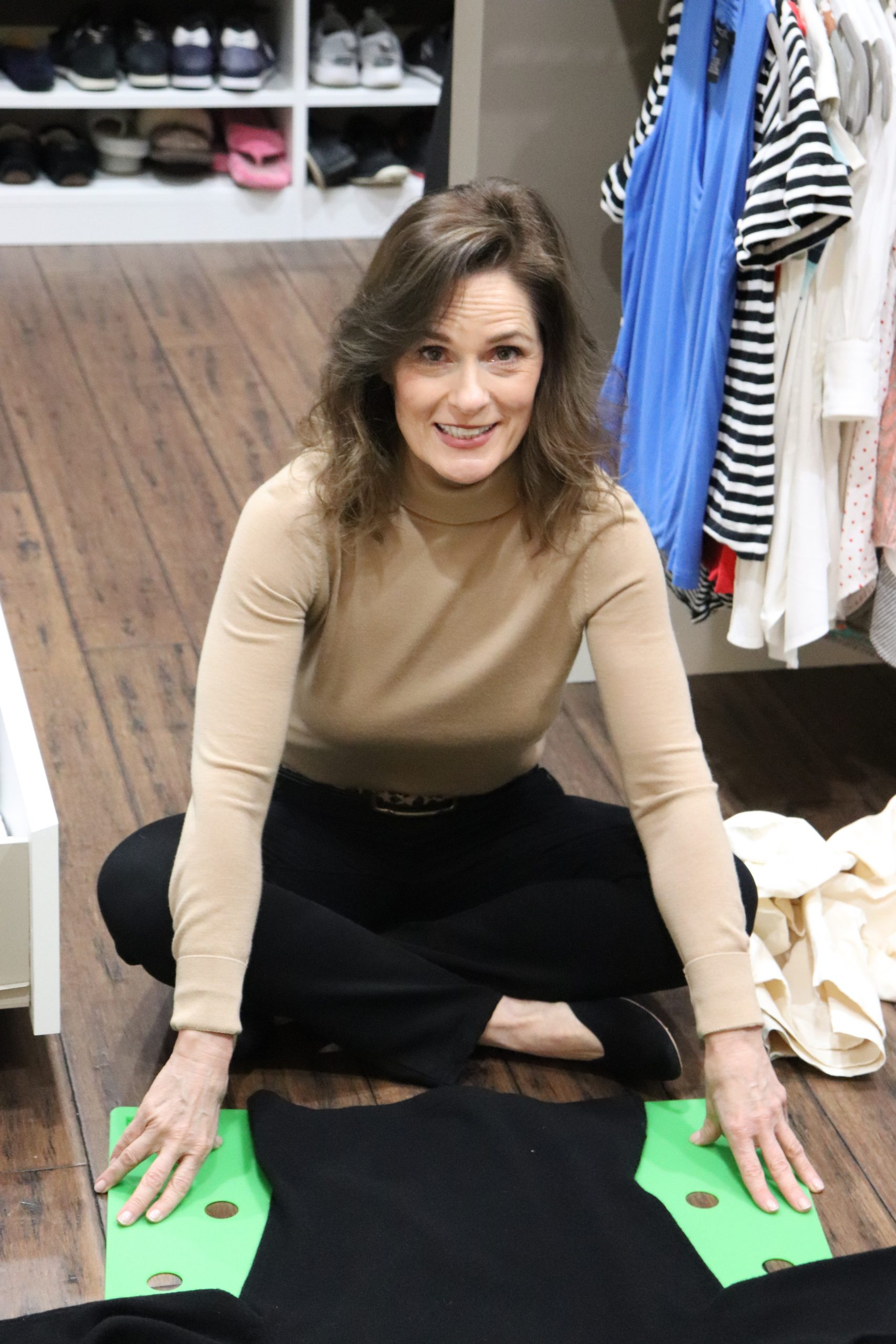 woman over 50 wearing a camel cashmere turtleneck and black jeans sitting on the floor of a closet folding a sweater with a plastic garment folder to demonstrate cashmere cleaning and storage love to your sweaters
