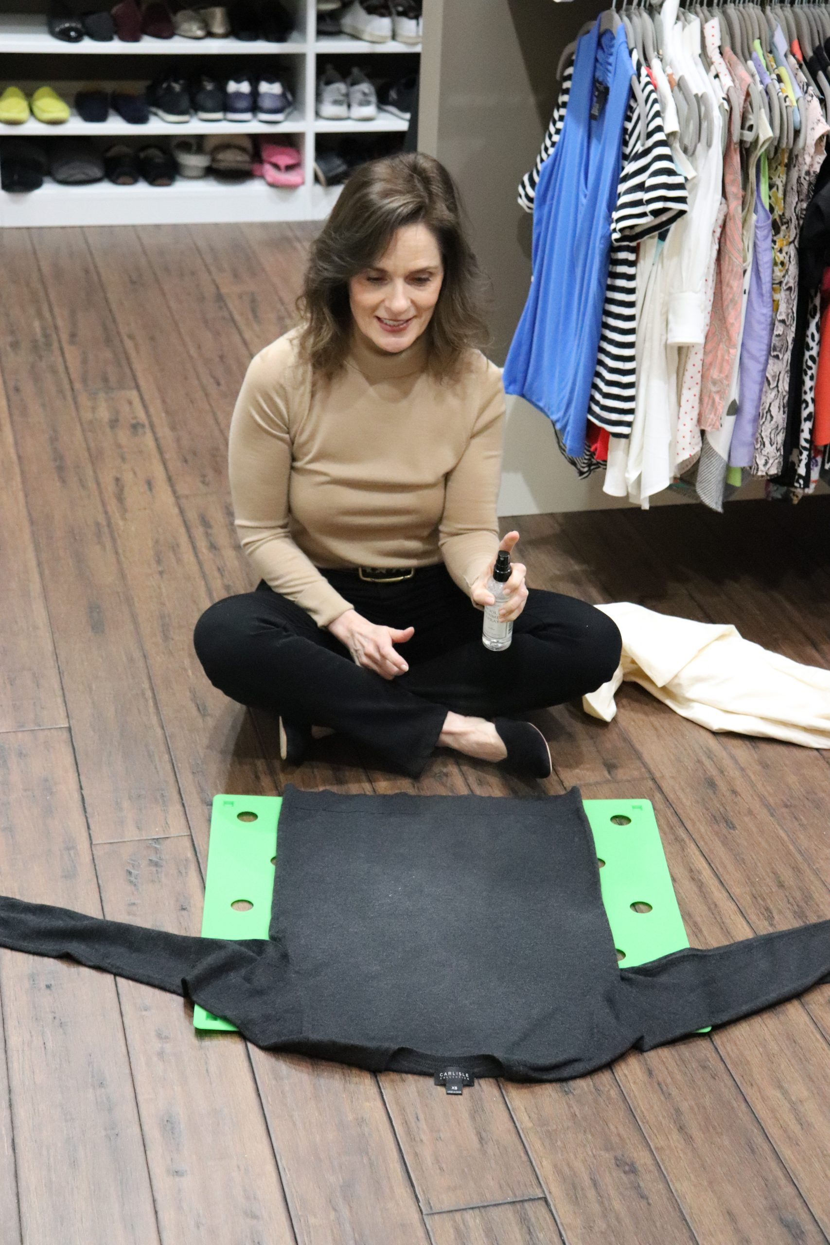woman over 50 wearing a camel cashmere turtleneck sweater and black jeans sitting on the floor of a closet spraying a sweater to explain how to show cashmere cleaning and storage love tips