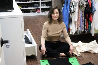 woman over 50 sitting on the floor of a closet wearing a camel cashmere turtleneck sweater and black jeans folding a sweater using a garment folder