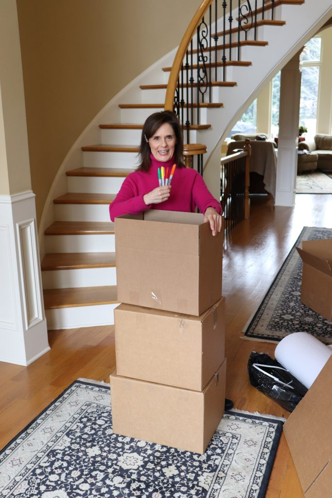 woman over 50 wearing a pink sweater holding colored markers on top of moving boxes we're moving