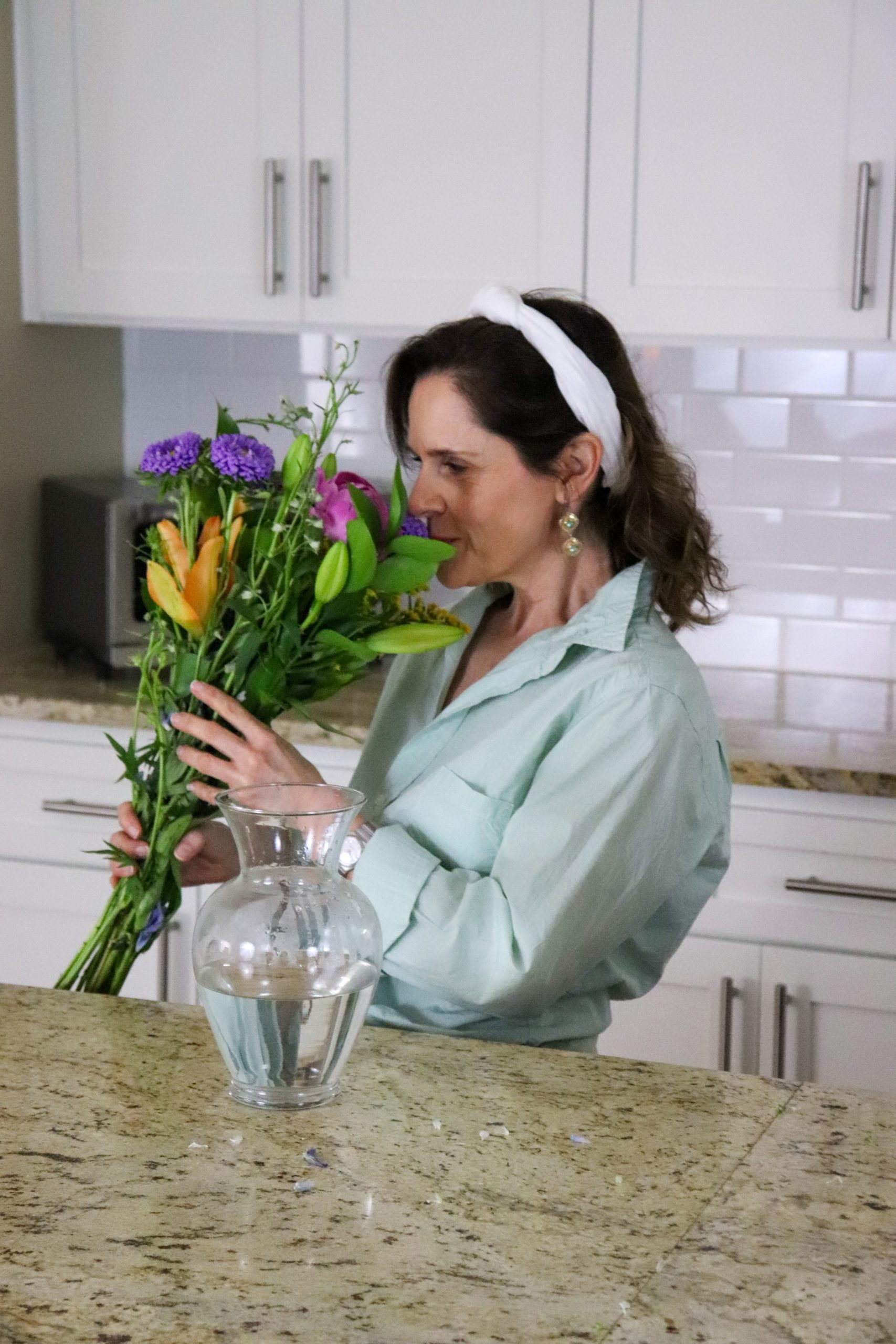 woman over 50 wearing a green shirt sniffing a boquet of May flowers