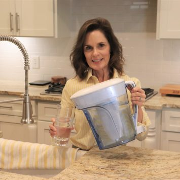 woman over 50 wearing a yellow and white striped blouse at a kitchen sink pouring a glass of water from a ZeroWater water pitcher from Amazon