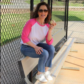 woman over 50 wearing a pink and white baseball style tshirt sitting on a dugout bench holding a baseball