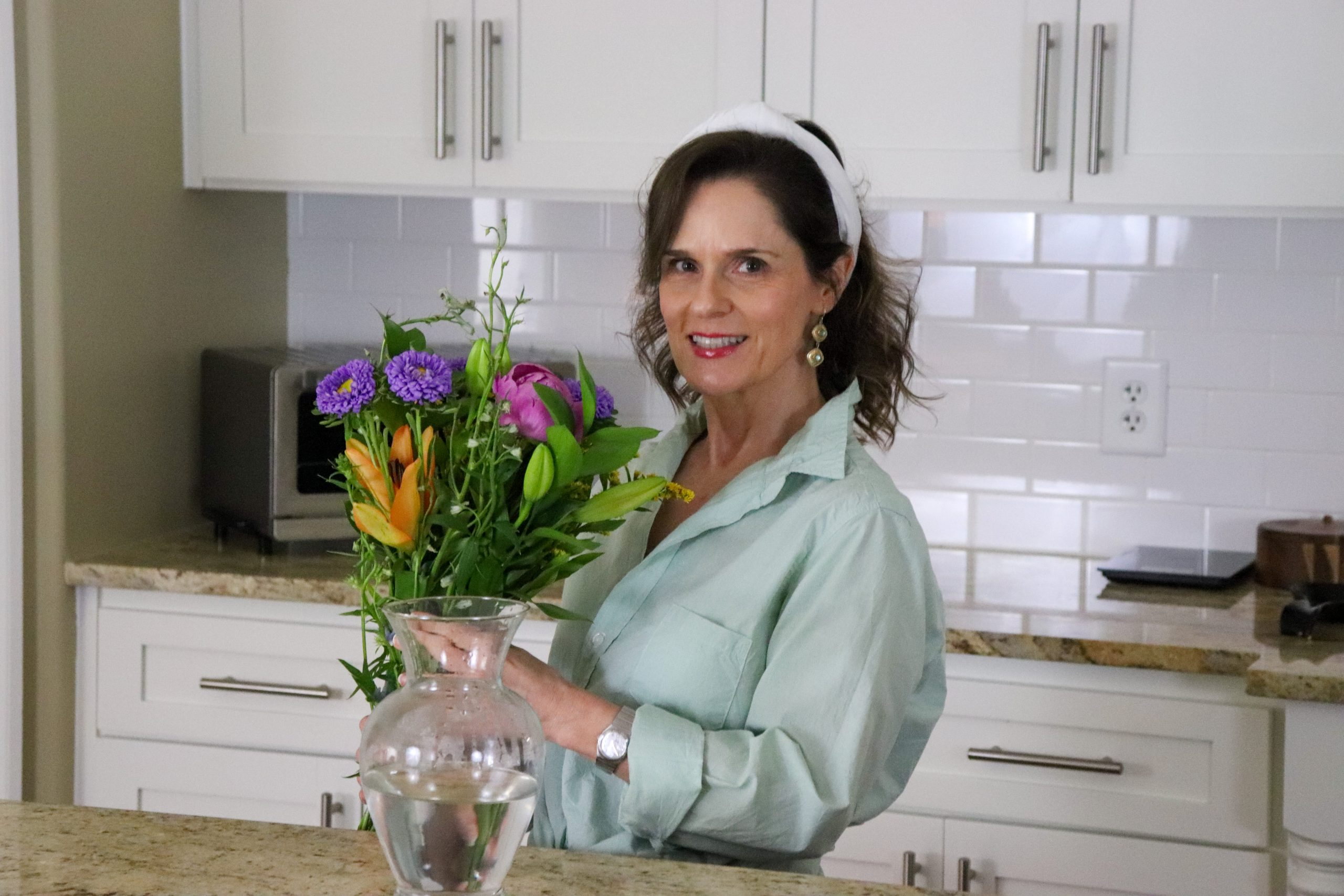 woman over 50 wearing a green shirt holding a bouquet of May flowers