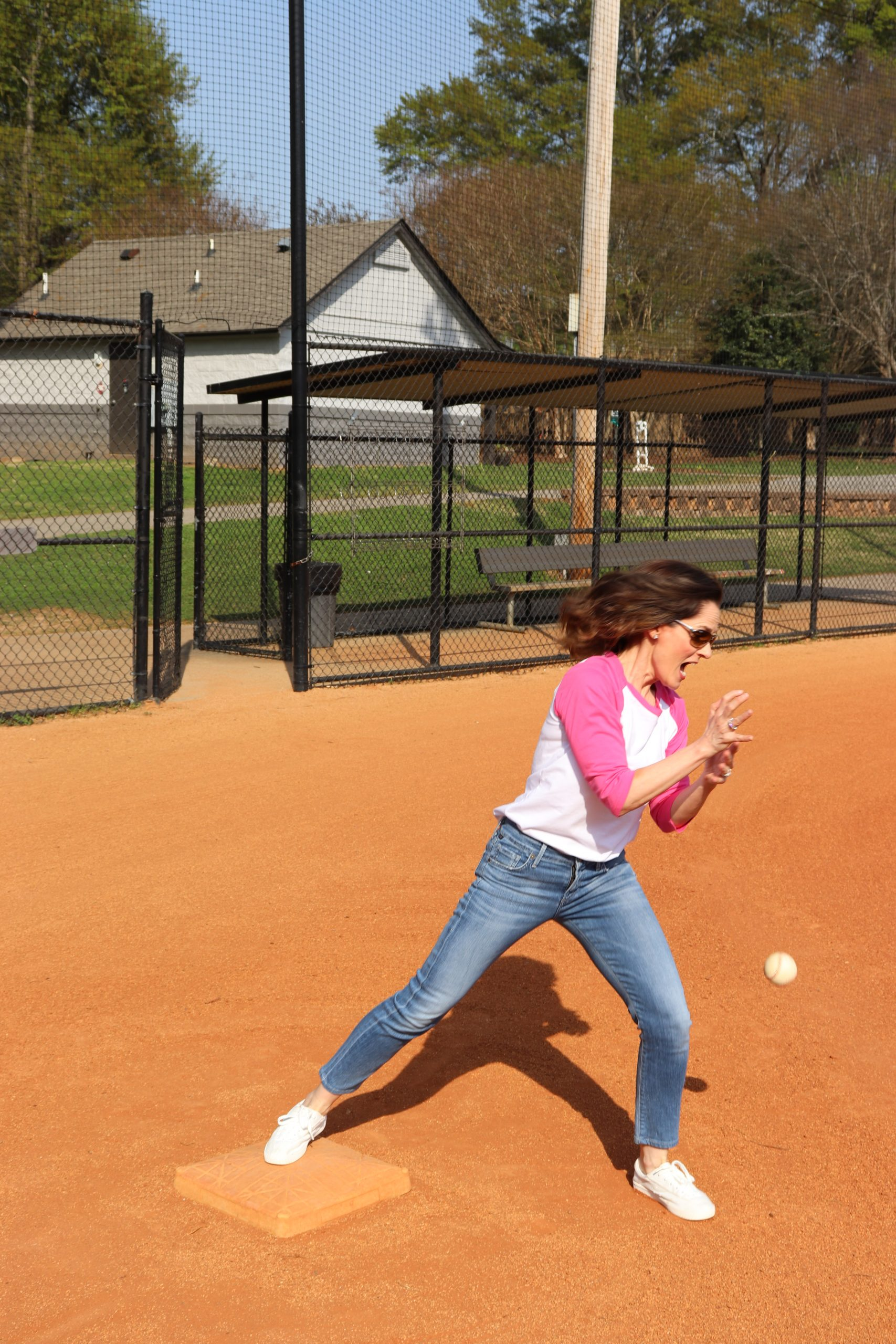 woman over 50 standing on a baseball field trying to catch a curveball