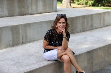 woman over 50 wearing a black top and white bermuda shorts sitting on a concrete step