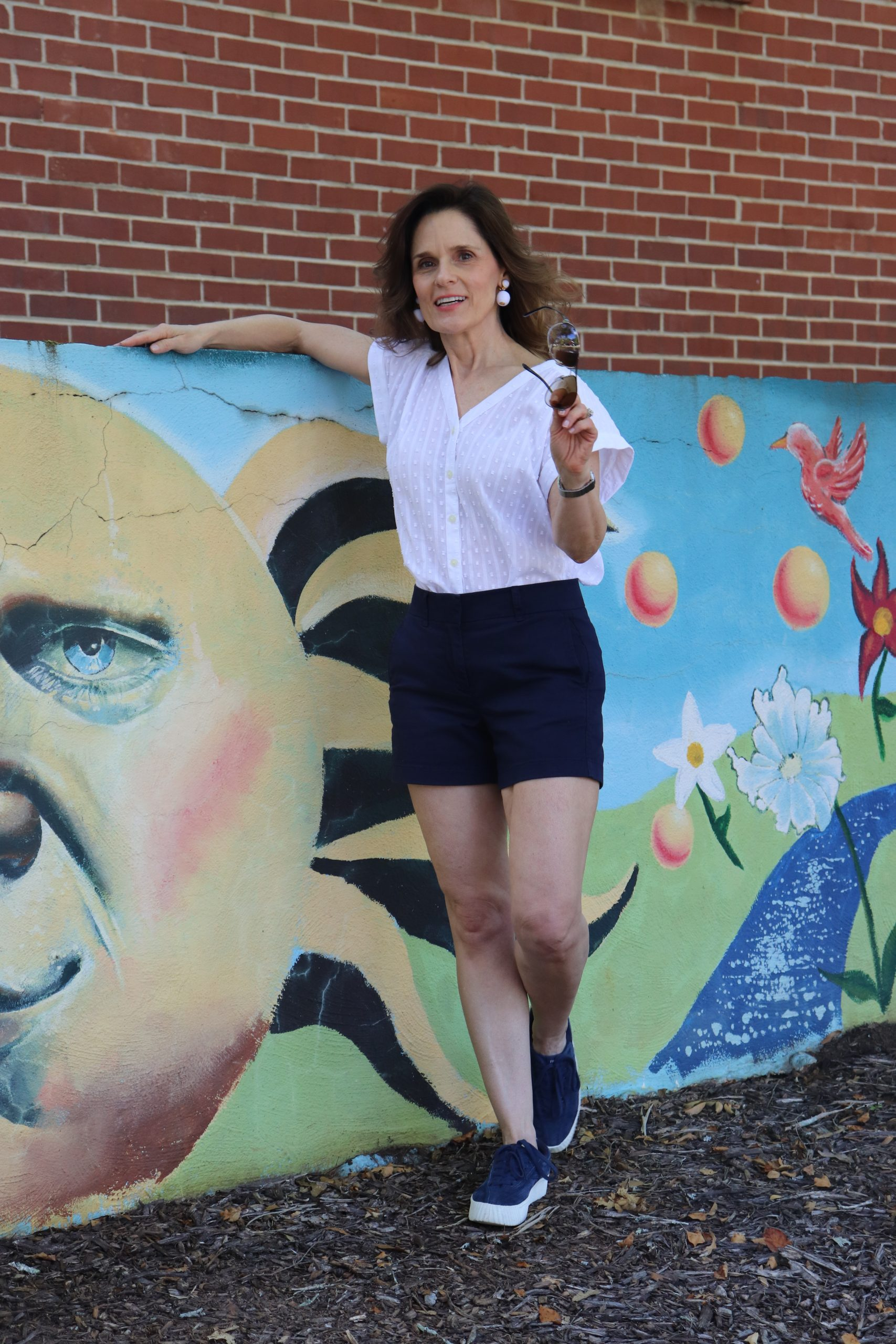 woman over 50 standing in front of a mural wearing a white top and shorts