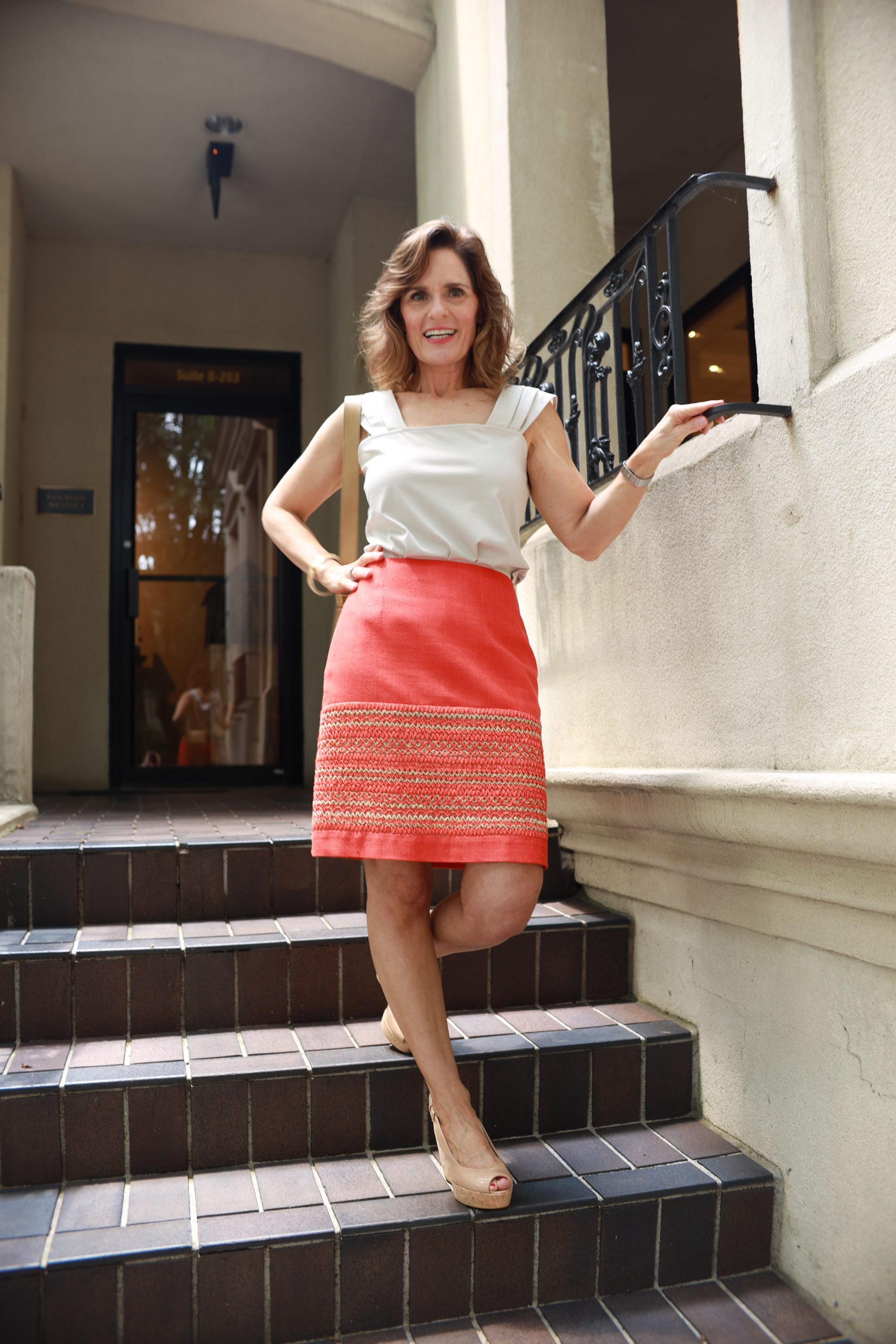 woman over 50 wearing a tan sleeveless blouse and an orange silk skirt that has an inset of tan and orange raffia