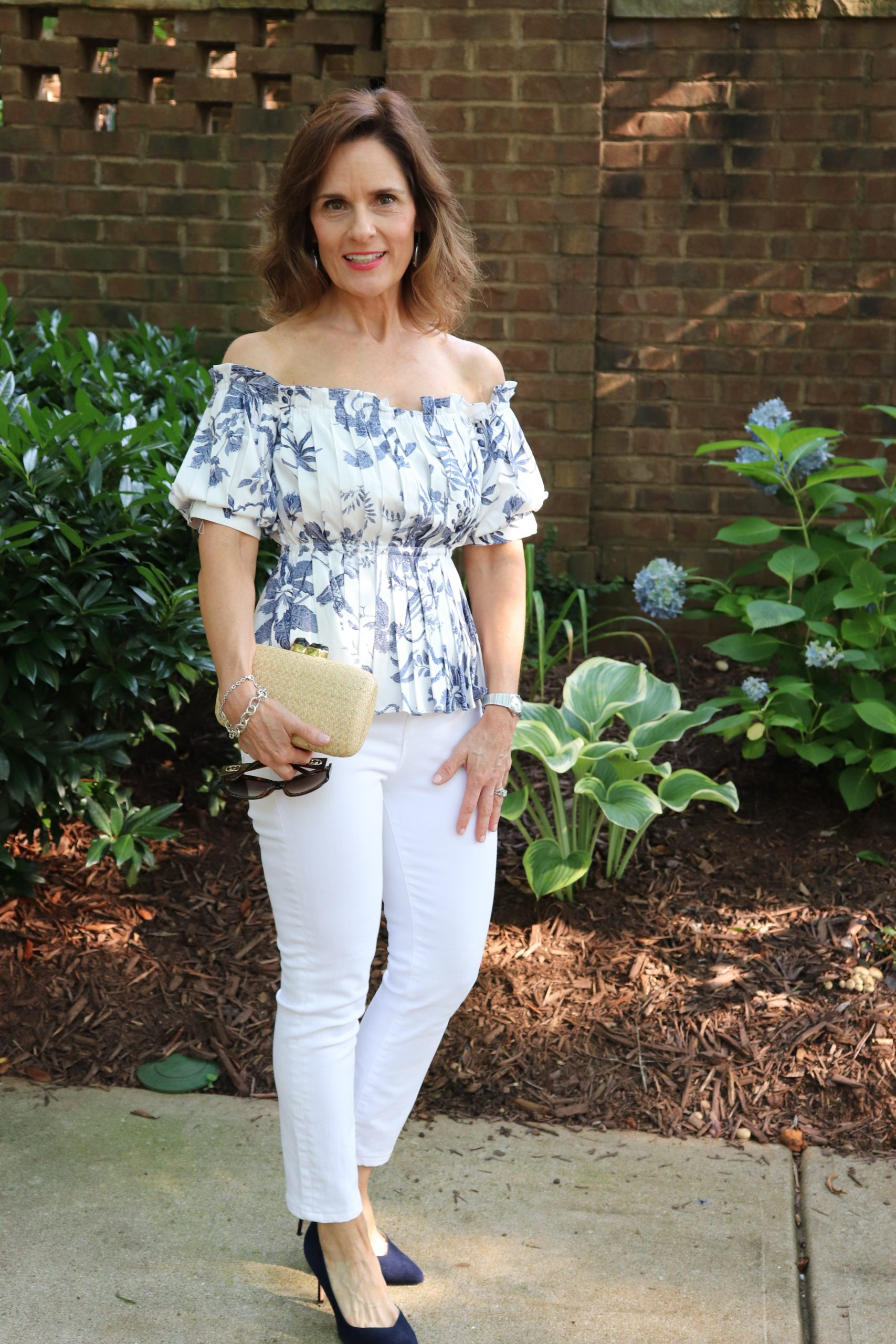 woman over 50 wearing a white off the shoulder top with blue flowers white denim, blue suede pumps, and carrying a small wicker handbag and glasses