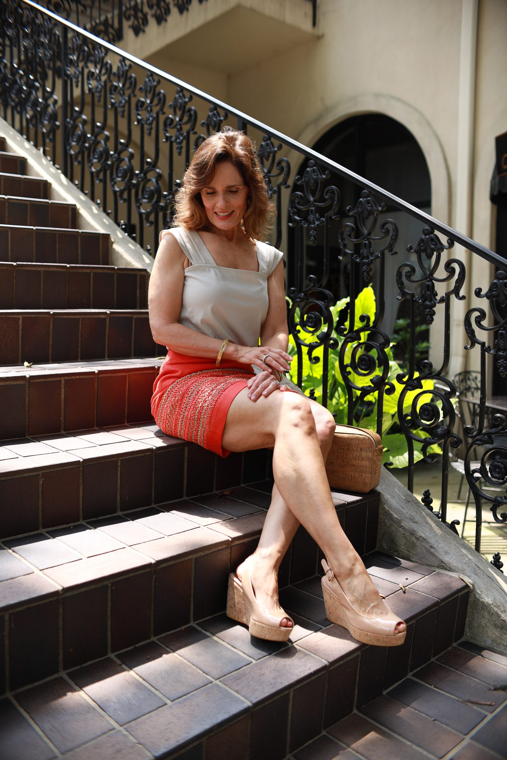 woman over 50 wearing an orange silk skirt that has an orange and tan raffia insert with a tan blouse sitting on a brick staircase next to rod iron railing