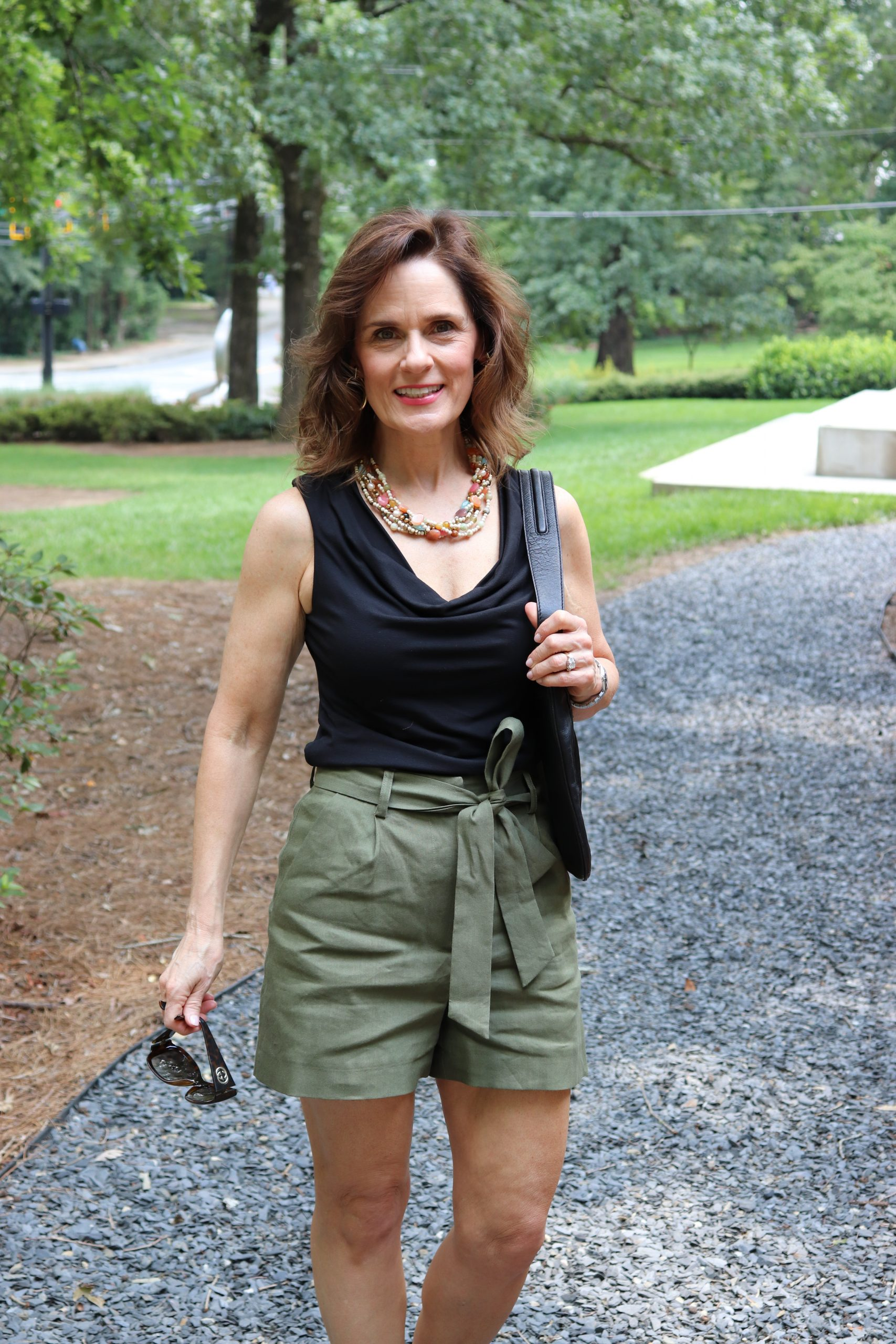 woman over 50 wearing summer neutrals that are a black sleeveless top and dark green shorts walking down a gravel path in a garden