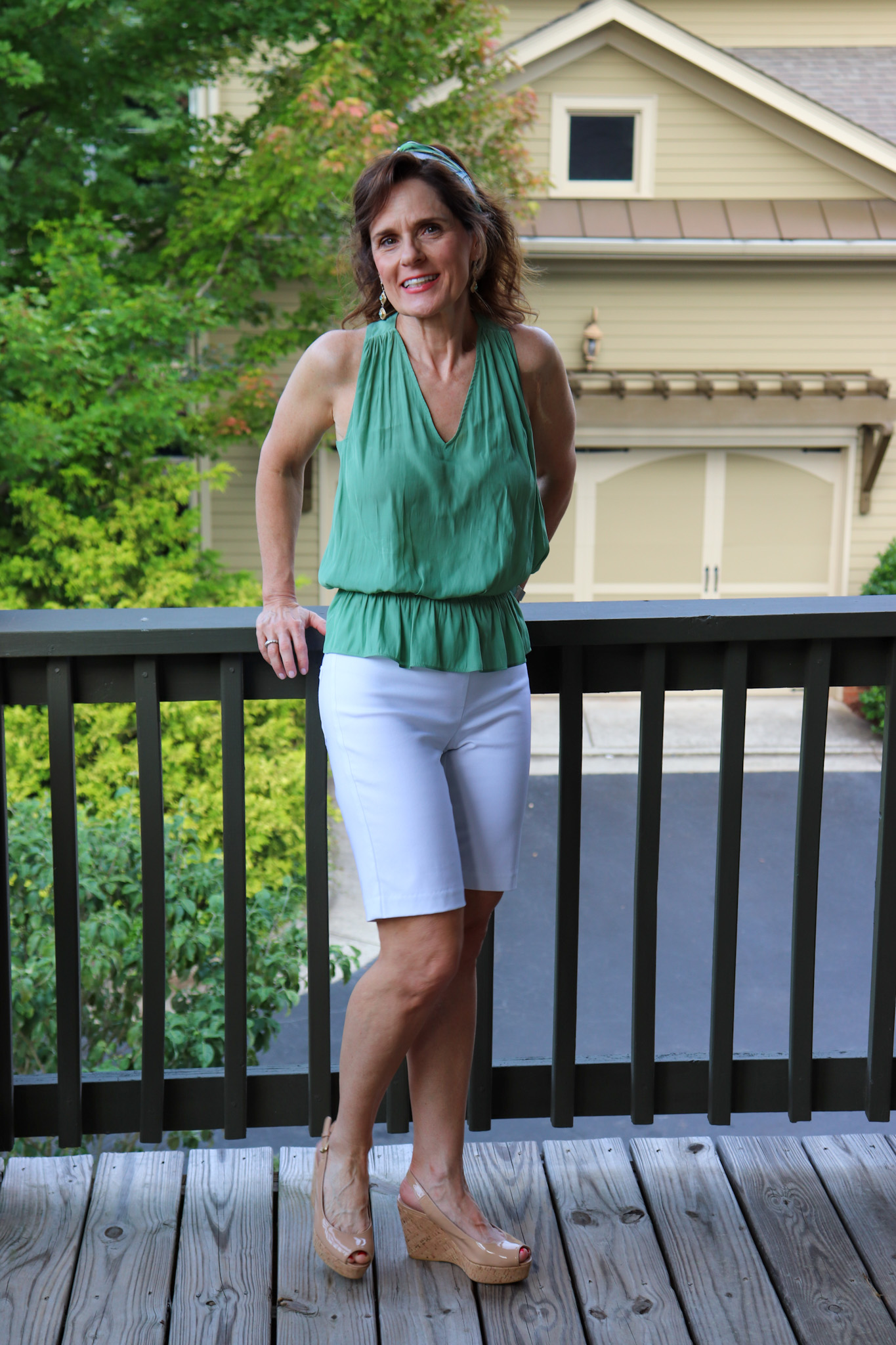 woman over 50 wearing a green sleeveless top , white bermuda shorts and a headband to pull her hair back to beat the humidity