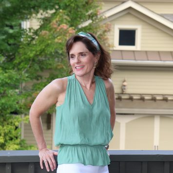 woman over 50 wearing a sleeveless green top and has her hair pulled back with a floral headband for winning the humidity battle