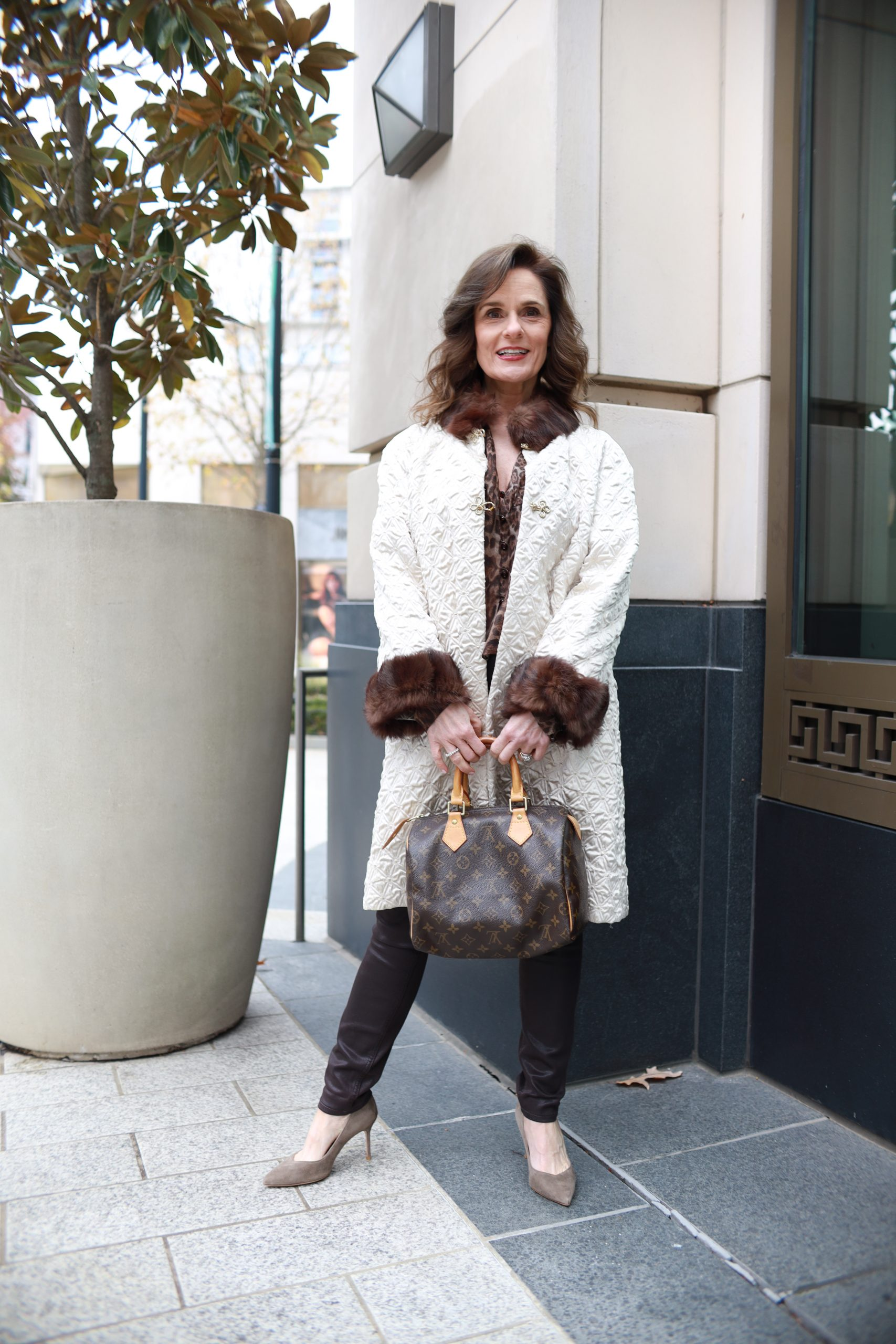 woman over 50 wearing a vintage cream colored coat trimmed in fur, brown skinny pants, carrying a Louis Vuitton handbag wearing neutral suede pumps pump perfection