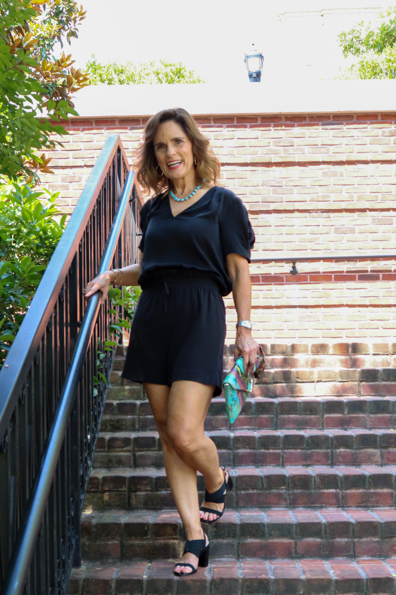 woman over 50 walking down a brick staircase wearing black summer silks, a short sleeve vneck top and shorts