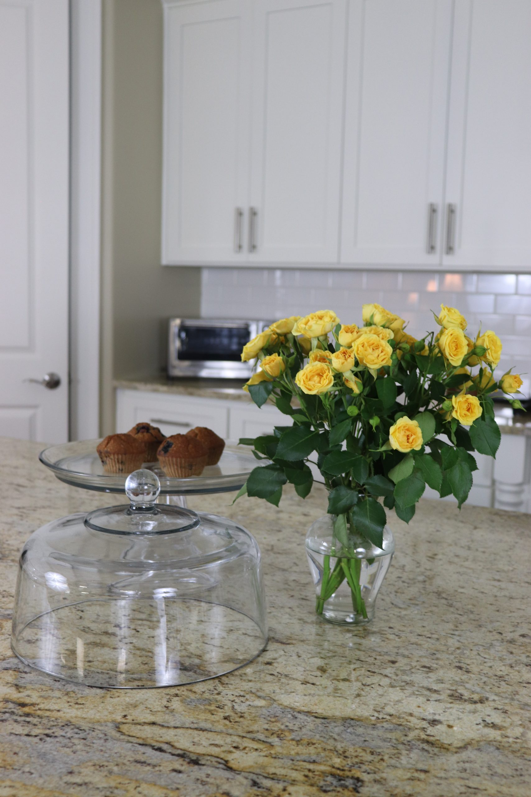 clear glass cake plate with the cover off sitting on a kitchen countertop next to a vase of yellow flowers muffins are breakfast meal prep item