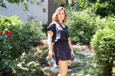 woman over 50 standing amongst green shrubbery wearing a black summer silk top and shorts