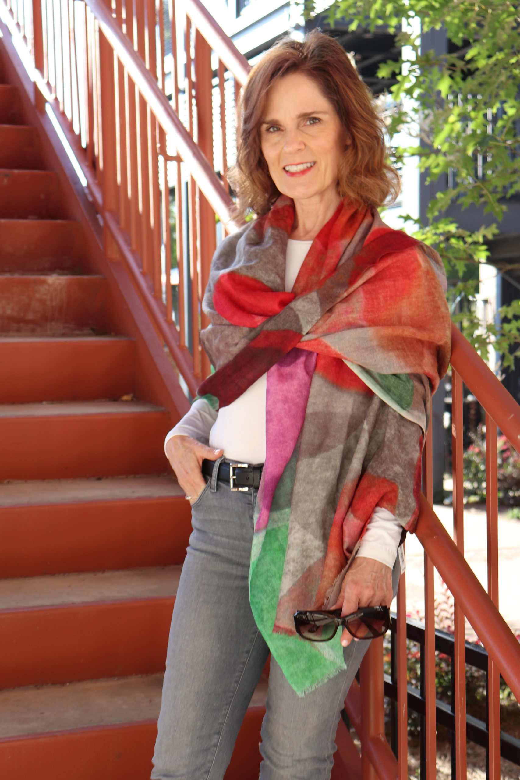 woman over 50 standing on an orange metal staircase leaning against the railing wrapped up for fall in a scarf with fall colors over a white long sleeve tee with jeans