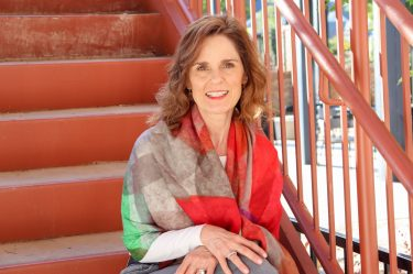 woman over 50 sitting on orange metal stairs wrapped up for fall in a scarf with fall colors