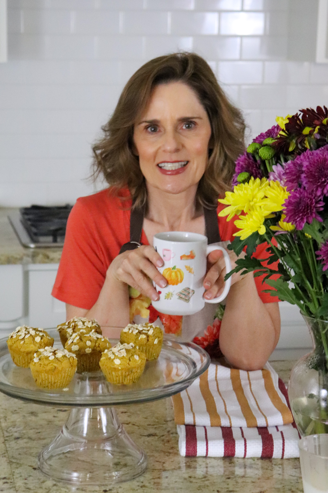 woman over 50 standing in front of a kitchen countertop holding a fall themed coffee mug and enjoying scents of the season, pumpkin apple muffins and fresh mums