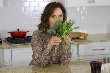 woman standing in a kitchen smelling a small vase of fresh herbs from a cutting garden